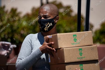 US actress Tiffany Haddish helps distribute computers to students in foster care during a drive-thru giveaway amid the coronavirus pandemic in Los Angeles, California, USA, 30 July 2020. The computers are donated by Wesson's 'OurCycleLA' project, a digital inclusion program designed to bridge the digital divide in low-income households in Los Angeles and other marginalized communities.