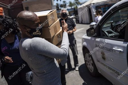 US actress Tiffany Haddish (L) helps distribute computers to students in foster care during a drive-thru giveaway amid the coronavirus pandemic in Los Angeles, California, USA, 30 July 2020.  The computers are donated by Wesson's 'OurCycleLA' project, a digital inclusion program designed to bridge the digital divide in low-income households in Los Angeles and other marginalized communities.