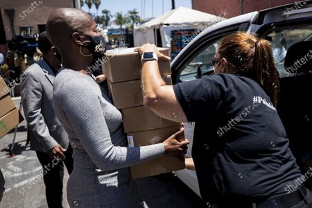 US actress Tiffany Haddish (L) and volunteers distribute computers to students in foster care during a drive-thru giveaway amid the coronavirus pandemic in Los Angeles, California, USA, 30 July 2020. The computers are donated by Wesson's 'OurCycleLA' project, a digital inclusion program designed to bridge the digital divide in low-income households in Los Angeles and other marginalized communities.
