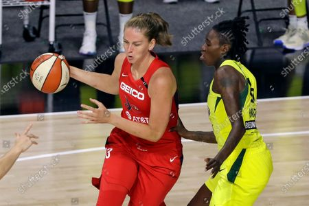 Washington Mystics forward Emma Meesseman (33) drives around Seattle Storm forward Natasha Howard (6) during the first half of a WNBA basketball game, in Bradenton, Fla