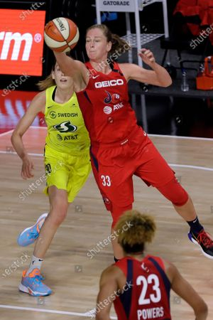 Washington Mystics forward Emma Meesseman (33) steals a pass intended for Seattle Storm forward Breanna Stewart (30) during the second half of a WNBA basketball game, in Bradenton, Fla