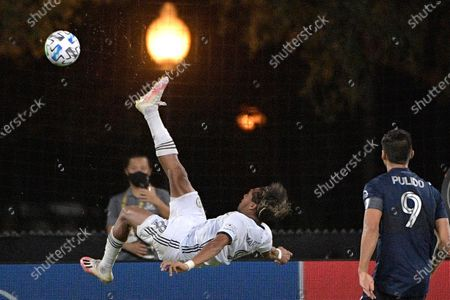 Philadelphia Union midfielder Jose Andres Martinez (8) performs a bicycle kick in front of Sporting Kansas City forward Alan Pulido (9) during the second half of an MLS soccer match, in Kissimmee, Fla
