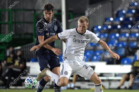 Philadelphia Union forward Kacper Przybylko, right, loses control of the ball in front of Sporting Kansas City midfielder Graham Smith (16) during the second half of an MLS soccer match, in Kissimmee, Fla