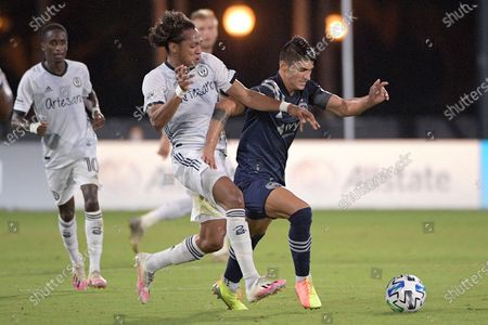 Philadelphia Union midfielder Jose Andres Martinez and Sporting Kansas City forward Alan Pulido, right, compete for a ball during the first half of an MLS soccer match, in Kissimmee, Fla