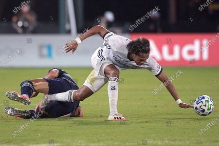 Sporting Kansas City forward Alan Pulido, left, and Philadelphia Union midfielder Jose Andres Martinez get tangled up while competing for a ball during the first half of an MLS soccer match, in Kissimmee, Fla