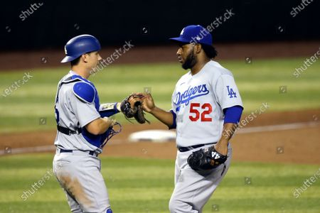 Los Angeles Dodgers relief pitcher Pedro Baez (52) celebrates with Dodgers catcher Will Smith, left, after the final out against the Arizona Diamondbacks during the ninth inning of the Diamondbacks' home opener baseball game, in Phoenix. The Dodgers defeated the Diamondbacks 6-3