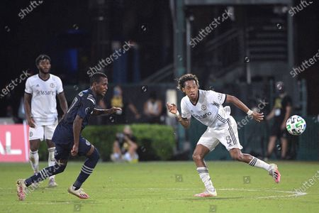 Sporting Kansas City midfielder Gadi Kinda (17) and Philadelphia Union midfielder Jose Andres Martinez (8) compete for a ball during the second half of an MLS soccer match, in Kissimmee, Fla