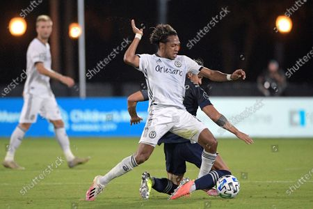 Philadelphia Union midfielder Jose Andres Martinez, front, and Sporting Kansas City forward Alan Pulido compete for a ball during the first half of an MLS soccer match, in Kissimmee, Fla