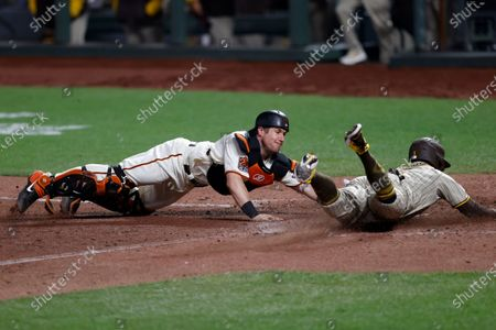 San Diego Padres Greg Garcia (R) slides safely into homeplate to score while beating the tag by San Francisco Giants catcher Tyler Heinman (L) during the 10th inning of their MLB game at Oracle Park, in San Francisco, California, USA, 30 July 2020. The start of the season was delayed due to the coronavirus pandemic and games are being held behind closed doors.