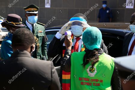 Zimbabwean President Emmerson Mnangagwa (C) gets his temperature checked before the burial of the late Zimbabwe minister of Agriculture, Perence Shiri at the National Heroes Acre in Harare, Zimbabwe, 31 July 2020. The minister died with covid-19 on 29th July 2020.