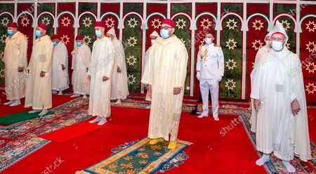 In this photo released by the Moroccan News Agency (MAP), Morocco's King Mohammed VI, third right, wears a face mask flanked by Morocco's Crown Prince Moulay El Hassan, third left, and Prince Moulay Rachid, second left, during the Eid Al Adha prayer at the Royal Residence in M'Diq, to mark Eid al-Adha, the most important holiday in the Muslim calendar