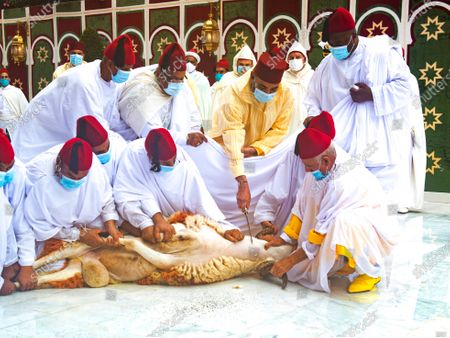 In this photo released by the Moroccan Royal Palace, Morocco's King Mohammed VI, center in yellow, wears a face mask during the sacrifice ritual, at the Royal Residence in M'Diq, to mark Eid al-Adha, the most important holiday in the Muslim calendar
