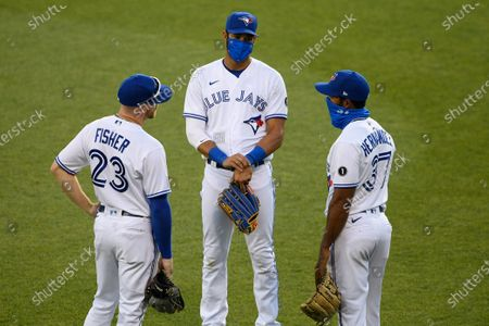 Toronto Blue Jays outfielders Derek Fisher (23), Lourdes Gurriel Jr., center, and Teoscar Hernandez (37) talk during a pitching change during the seventh inning of a baseball game against the Washington Nationals, in Washington. The Nationals won 4-0 in extra innings