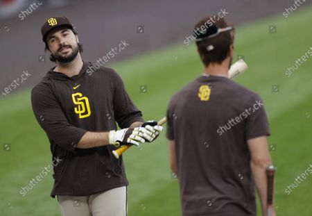 San Diego Padres second baseman Greg Garcia, left, jokes with center fielder Wil Myers as they wait for their turns in the cage during batting practice before a baseball game against the Colorado Rockies, in Denver