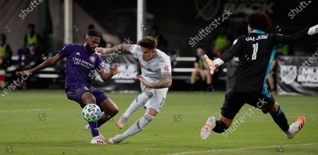 Orlando City defender Ruan, left, tries to stop Los Angeles FC midfielder Brian Rodriguez (17) as Orlando City goalkeeper Pedro Gallese (1) tries to make a block during the first half of an MLS soccer match, in Orlando, Fla