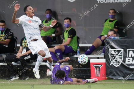 Los Angeles FC midfielder Mark-Anthony Kaye, left, collides with Orlando City defender Ruan, on ground, during the first half of an MLS soccer match, in Orlando, Fla