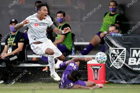 Los Angeles FC midfielder Mark-Anthony Kaye, left, collides with Orlando City defender Ruan as he tries to move the ball towards his goal during the first half of an MLS soccer match, in Orlando, Fla