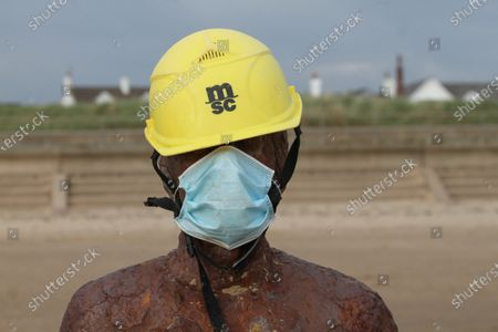 One of Sir Antony Gormley Iron men draped in a hard hat and a face mask at Crosby Beach. The Government has made it mandatory to wear face coverings in all public transport, supermarkets and indoor shopping centers as a measure to combat the spread of the novel coronavirus.