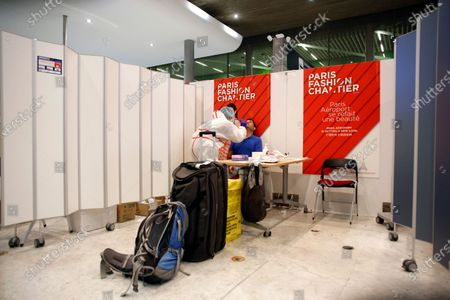 Health worker collects a nasal swab sample for COVID-19 test, at the Roissy Charles de Gaulle airport, outside Paris, . Travelers entering France from 16 countries where the coronavirus is circulating widely are having to undergo virus tests upon arrival at French airports and ports