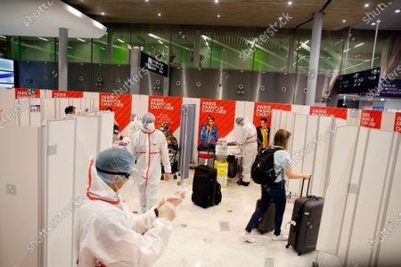 Passenger leaves after being tested with a COVID-19 test, at the Roissy Charles de Gaulle airport, outside Paris, . Travelers entering France from 16 countries where the coronavirus is circulating widely are having to undergo virus tests upon arrival at French airports and ports