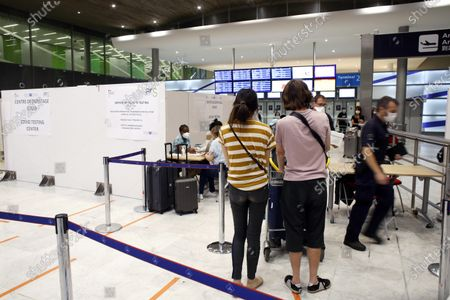 People register prior to be tested with the COVID-19 test, at the Roissy Charles de Gaulle airport, outside Paris, . Travelers entering France from 16 countries where the coronavirus is circulating widely are having to undergo virus tests upon arrival at French airports and ports