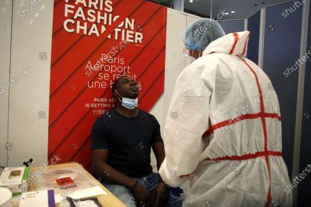 Health worker is going to collect a nasal swab sample for COVID-19 test, at the Roissy Charles de Gaulle airport, outside Paris, . Travelers entering France from 16 countries where the coronavirus is circulating widely are having to undergo virus tests upon arrival at French airports and ports