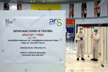 Health workers wait to test passengers with the COVID-19 test, at the Roissy Charles de Gaulle airport, outside Paris, . Travelers entering France from 16 countries where the coronavirus is circulating widely are having to undergo virus tests upon arrival at French airports and ports