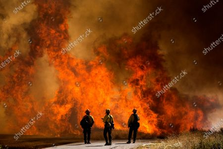 Firefighters watch as flames flare at the Apple Fire in Cherry Valley, Calif., . A wildfire northwest of Palm Springs flared up Saturday afternoon, prompting authorities to issue new evacuation orders as firefighters fought the blaze in triple-degree heat