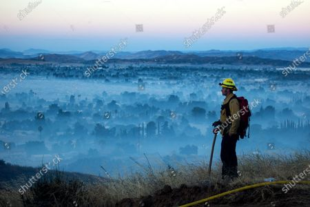 Firefighter watches a brush fire at the Apple Fire in Cherry Valley, Calif