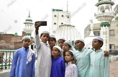 Children pose for a photograph after offering Eid-ul-Adha prayers, at Khairudeen Mosque, on August 1, 2020 in Amritsar, India. The holy festival of sacrifice, which falls on the 10th day of Dhu al-Hijjah as per the Islamic lunar calendar, is being celebrated today. Bakra Eid or Bakrid is marked by sacrificing an animal that is close to them to prove their devotion and love for Allah. Post the sacrifice, devotees distribute the offering to family, friends, neighbours and especially to the poor and the needy.
