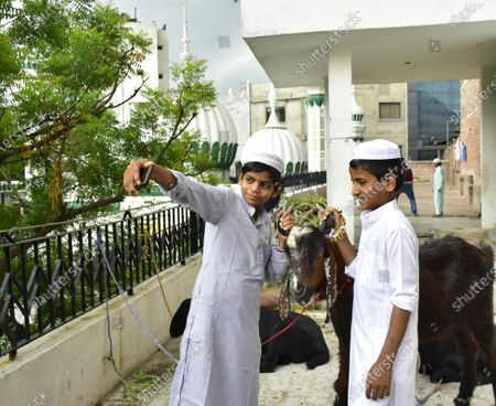 Children pose for a photograph with their goats after offering Eid-ul-Adha prayers, at Khairudeen Mosque, on August 1, 2020 in Amritsar, India. The holy festival of sacrifice, which falls on the 10th day of Dhu al-Hijjah as per the Islamic lunar calendar, is being celebrated today. Bakra Eid or Bakrid is marked by sacrificing an animal that is close to them to prove their devotion and love for Allah. Post the sacrifice, devotees distribute the offering to family, friends, neighbours and especially to the poor and the needy.