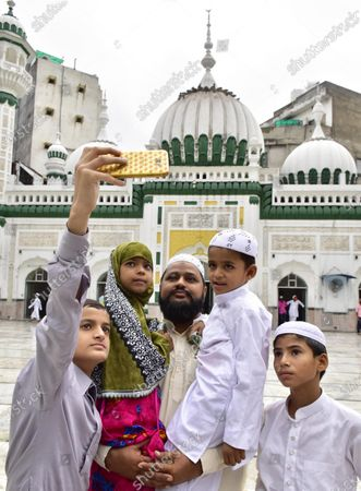 A man poses with children for a photograph after offering Eid-ul-Adha prayers, at Khairudeen Mosque, on August 1, 2020 in Amritsar, India. The holy festival of sacrifice, which falls on the 10th day of Dhu al-Hijjah as per the Islamic lunar calendar, is being celebrated today. Bakra Eid or Bakrid is marked by sacrificing an animal that is close to them to prove their devotion and love for Allah. Post the sacrifice, devotees distribute the offering to family, friends, neighbours and especially to the poor and the needy.