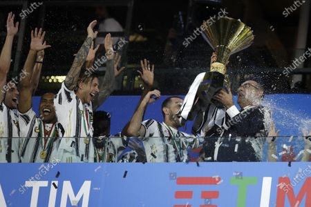 Juventus' head coach Maurizio Sarri, right, holds up the trophy while Juventus players celebrate winning an unprecedented ninth consecutive Italian Serie A soccer title, at the end of the a Serie A soccer match between Juventus and Roma, at the Allianz stadium in Turin, Italy, Saturday, Aug.1, 2020