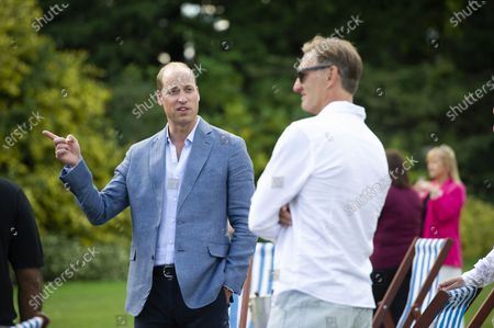 Britain's Prince William, left, talks with former Arsenal footballer Tony Adams, during a screening of the Heads Up FA Cup Final between Arsenal and Chelsea, at the Sandringham Estate to mark the culmination of the Heads Up campaign, in Norfolk, England
