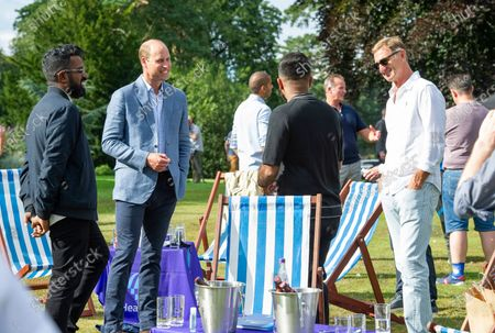 Britain's Prince William, second left, talks with Romesh Ranganathan, left and former Arsenal player Tony Adams, during a screening of the Heads Up FA Cup Final between Arsenal and Chelsea, at the Sandringham Estate to mark the culmination of the Heads Up campaign, in Norfolk, England