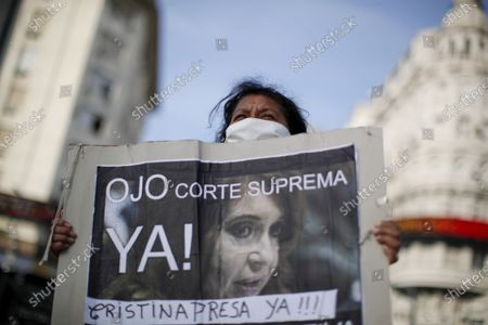 """Woman holds a poster featuring an image of Vice President Cristina Fernandez with a message that reads in Spanish: """" Be careful Supreme Court. Imprison Cristina now!"""", during a protest against a justice reform initiative by President Alberto Fernandez that demonstrators say would give impunity to Cristina Fernandez who is under investigation, in Buenos Aires, Argentina"""