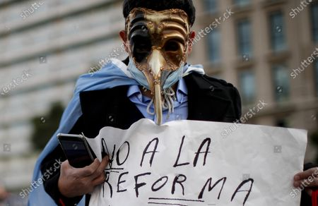 """Man holds a poster with a message that reads in Spanish: """"No to the reform"""", during a protest against a justice reform initiative by President Alberto Fernandez that demonstrators say would give impunity to Vice President Cristina Fernandez who is under investigation, in Buenos Aires, Argentina"""