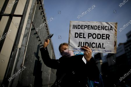 """Woman holds a poster with a message that reads in Spanish: """"Independence of judicial power"""" during a protest against a justice reform initiative by President Alberto Fernandez that demonstrators say would give impunity to Vice President Cristina Fernandez who is under investigation, in Buenos Aires, Argentina"""