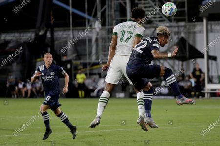 Portland Timbers forward Jeremy Ebobisse, heads the ball away from New York City defender Ronald Matarrita during the first half of an MLS soccer match, in Kissimmee, Fla