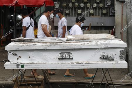 """People pass by an empty coffin placed outside a public market to remind people to stay home as the government relaxes quarantine measures against the COVID19 on in Manila, Philippines. Coronavirus infections in the Philippines continues to surge Sunday as medical groups declared the country was waging """"a losing battle"""" against the contagion and asked the president to reimpose a lockdown in the capital"""