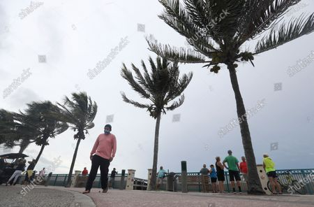 People gather to watch the strong waves on the beach as palm trees sway in the wind, in Vero Beach, Fla. Isaias weakened from a hurricane to a tropical storm late Saturday afternoon, but was still expected to bring heavy rain and flooding as it barrels toward Florida