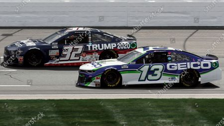 Driver Corey LaJoie (32) races beside Ty Dillon (13) during a NASCAR Cup Series auto race, at the New Hampshire Motor Speedway in Loudon, N.H