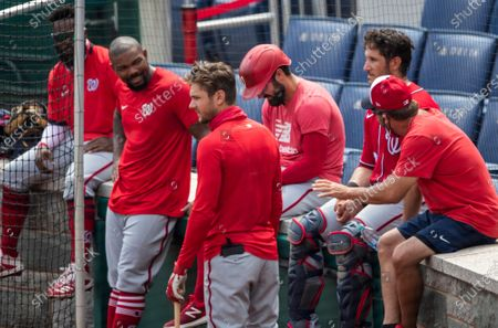 Washington Nationals, from second left to right, Howie Kendrick, Trea Turner, Adam Eaton, and Yan Gomes, watch from the sideline during a baseball intrasquad game at Nationals Park, in Washington