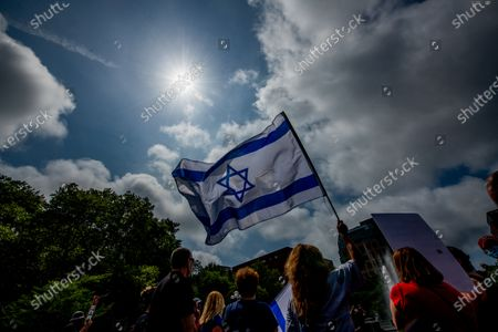Demonstrators hold signs as they assemble in a show of solidarity with the protests in Israel against the government and Prime Minister Benjamin (Bibi) Netanyahu in Washington Square Park