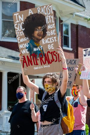 """Stock Photo of Protester Emma Varano holds a sign with an Angela Davis quote during a Black Lives Matter protest march in rural Pennsylvania. The Milton-based anti-racist collective """"If Not Us, Then Who?"""" organized the protest and led about 200 people on a march through the streets of Watsontown. Protesters were confronted by several dozen counter-protesters who gathered in front of the Mansion House Bar and Grill."""