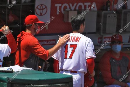 Los Angeles Angels designated hitter Shohei Ohtani, of Japan, gets a pat on the back from a teammate after being taken out of the game during the second inning of a baseball game against the Houston Astros, in Anaheim, Calif