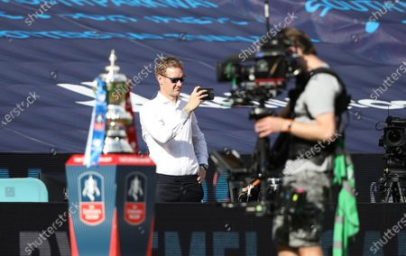 Stock Photo of Dan Walker, from BBC Sport, behind the FA Cup at the Emirates FA Cup Final match Arsenal v Chelsea, at Wembley Stadium, London, UK on 1st August, 2020.