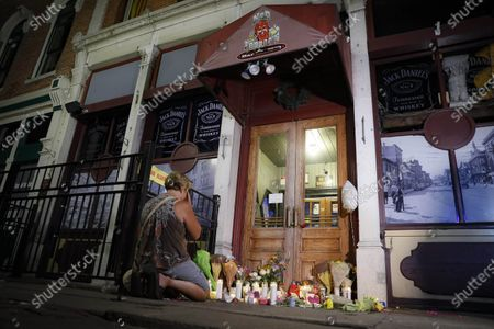 FILE-Mourners visit a makeshift memorial, outside Ned Peppers bar following a vigil at the scene of the mass shooting in Dayton, Ohio. As the anniversary of the 2019 shooting approaches, the mayor talks about plans to mark the day, Dion Green whose father died in the mass shooting on a night with him, wrote a book about surviving tornadoes that shooting and new murals adorn the walls of buildings in the city's Oregon Entertainment District