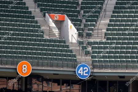Numbers for Jackie Robinson (42) and Cal Ripken Jr. (8) are seen near empty stands at Oriole Park at Camden Yards during the eighth inning of a baseball game between the Baltimore Orioles and the Tampa Bay Rays, Sun, in Baltimore. The Orioles won 5-1