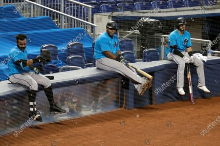 Miami Marlins' Jonathan Villar, left, Jesus Aguilar, center, and Jon Berti wait to bat during a baseball scrimmage at Marlins Park in Miami. Marlins CEO Derek Jeter blamed the team's coronavirus outbreak on a collective false sense of security that made players lax about social distancing and wearing masks. Infected were 21 members of the team's traveling party, including at least 18 players. None is seriously ill, Jeter said Monday, and he expects all to return this season
